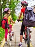 Muestra de la trayectoria de la bicicleta con los niños Muchachas que llevan el casco con la mochila Fotos de archivo