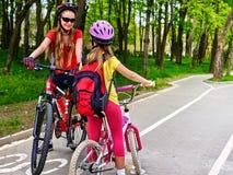 Muestra de la trayectoria de la bicicleta con los niños Muchachas que llevan el casco con la mochila Fotos de archivo libres de regalías