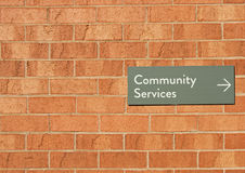 Muestra de los servicios comunitarios en una pared de ladrillo roja Imagen de archivo libre de regalías