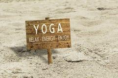 Muestra de madera de la yoga en una playa de la arena Imagen de archivo
