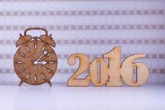 Muestra de madera del despertador y de la inscripción de 2016 años en lila Fotografía de archivo