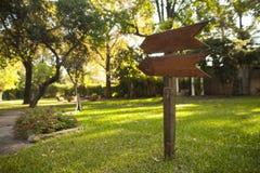 Muestra de madera del jardín que señala abajo de la trayectoria Imagen de archivo