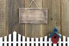 Muestra de madera en blanco que cuelga sobre la valla de estacas blanca con la pajarera Imagenes de archivo
