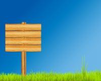 Muestra de madera en hierba Imagen de archivo libre de regalías