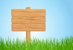 Muestra de madera en hierba verde Imagenes de archivo