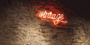 Muestra de neón del vintage en la pared de ladrillos rojos vieja foto de archivo