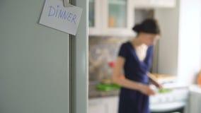 Muestra de papel de la cena en cookinf blured de la mujer del fondo en la cocina en casa almacen de metraje de vídeo