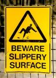 Muestra de peligro: GUÁRDESE DE LA SUPERFICIE RESBALADIZA con la imagen de caer del hombre Imagenes de archivo