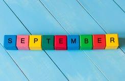 Muestra de septiembre en los cubos de madera del color con la luz Foto de archivo libre de regalías