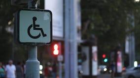 Muestra de una persona discapacitada que se sienta en una silla de ruedas contra la perspectiva de gente que camina borrosa Idea  metrajes