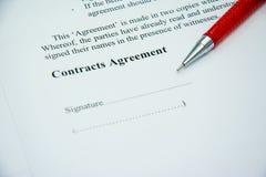 Muestra del acuerdo de contratos en el papel del documento con la pluma roja Fotos de archivo