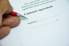 Muestra del acuerdo de contratos en el papel del documento con la pluma roja Fotografía de archivo