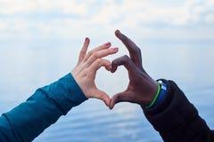 Muestra del amor Las manos blancas y negras hacen símbolo del corazón Imagen de archivo