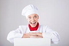 Muestra del cocinero Cocinero/panadero de la mujer que mira sobre la cartelera de papel de la muestra Mujer sorprendida y diverti Foto de archivo libre de regalías