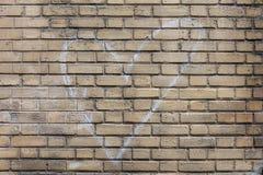 Muestra del corazón dibujada por la tiza blanca en la pared de ladrillo Fotos de archivo libres de regalías