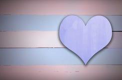 Muestra del corazón púrpura en la madera retra azul y rosada Imagen de archivo