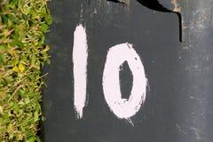 Muestra del número de casa 10 pintada en compartimiento plástico Fotos de archivo