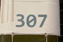 Muestra del número de casa 307 pintada en la pared Imágenes de archivo libres de regalías