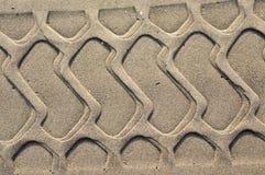 Muestra del neumático en la arena Fondo con la arena fina beige Enarene la superficie en la playa, visión desde arriba imágenes de archivo libres de regalías