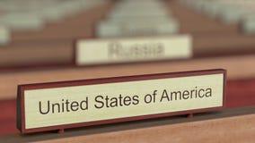 Muestra del nombre de los Estados Unidos de América entre placas de los países diferentes en la organización internacional stock de ilustración