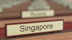 Muestra del nombre de Singapur entre placas de los países diferentes en la organización internacional metrajes