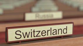Muestra del nombre de Suiza entre placas de los países diferentes en la organización internacional stock de ilustración