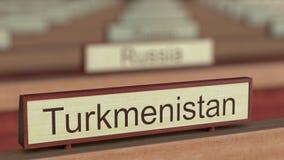 Muestra del nombre de Turkmenistán entre placas de los países diferentes en la organización internacional stock de ilustración