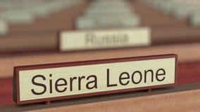 Muestra del nombre del Sierra Leone entre placas de los países diferentes en la organización internacional metrajes
