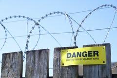 Muestra del peligro de la seguridad de la protección de la cerca de alambre de la maquinilla de afeitar en solar de la construcci fotografía de archivo