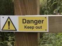 Muestra del peligro, en la cerca de madera Foto de archivo libre de regalías