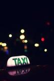 Muestra del taxi en la noche Foto de archivo libre de regalías