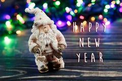 Muestra del texto de la Feliz Año Nuevo en el juguete de Papá Noel de la Navidad en backgro Imágenes de archivo libres de regalías
