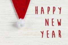 Muestra del texto de la Feliz Año Nuevo en el sombrero de santa de la Navidad en rústico blanco Fotos de archivo libres de regalías