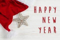 Muestra del texto de la Feliz Año Nuevo en la estrella de la Navidad y el sombrero de oro de santa Fotos de archivo libres de regalías