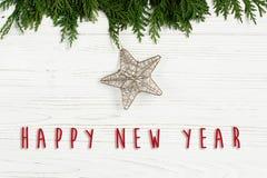Muestra del texto de la Feliz Año Nuevo en la estrella de oro de la Navidad en árbol verde Fotografía de archivo