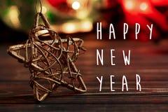 Muestra del texto de la Feliz Año Nuevo en la estrella de oro de la Navidad en fondo Foto de archivo libre de regalías