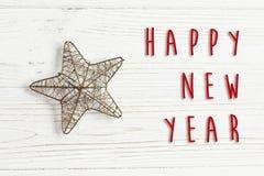 Muestra del texto de la Feliz Año Nuevo en la estrella de oro de la Navidad en whi elegante Foto de archivo libre de regalías