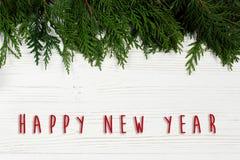 Muestra del texto de la Feliz Año Nuevo en la frontera de las ramas de árbol de navidad en el st Imagen de archivo libre de regalías