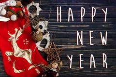 Muestra del texto de la Feliz Año Nuevo en los juguetes elegantes de oro de la Navidad en el re Fotos de archivo libres de regalías