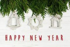Muestra del texto de la Feliz Año Nuevo en los juguetes simples de la Navidad en árbol verde Foto de archivo libre de regalías