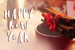 Muestra del texto de la Feliz Año Nuevo en los palillos de canela con la cinta en c roja Fotos de archivo