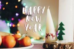 Muestra del texto de la Feliz Año Nuevo en la tabla rústica de la Navidad con la vela w Imagen de archivo