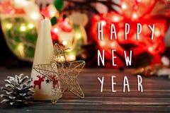 Muestra del texto de la Feliz Año Nuevo en vela de la Navidad y juguetes en backgr Fotos de archivo libres de regalías