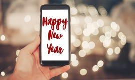 Muestra del texto de la Feliz Año Nuevo a mano que sostiene el teléfono elegante con vacío Imágenes de archivo libres de regalías