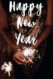 Muestra del texto de la Feliz Año Nuevo, tarjeta de felicitación mano que lleva a cabo un s ardiente Fotografía de archivo libre de regalías