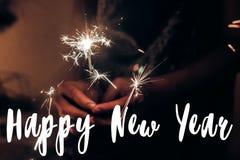 Muestra del texto de la Feliz Año Nuevo, tarjeta de felicitación mano que lleva a cabo un s ardiente Foto de archivo libre de regalías
