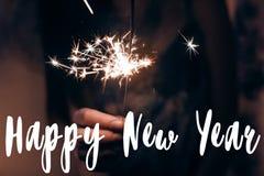 Muestra del texto de la Feliz Año Nuevo, tarjeta de felicitación mano que lleva a cabo una f ardiente Fotos de archivo