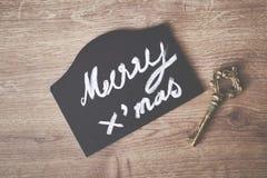 Muestra del texto de la Feliz Navidad con el cono del pino y el ornamento de la llave Fotos de archivo libres de regalías