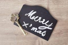 Muestra del texto de la Feliz Navidad con el cono del pino y el ornamento de la llave Foto de archivo