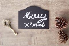 Muestra del texto de la Feliz Navidad con el cono del pino y el ornamento de la llave Fotografía de archivo